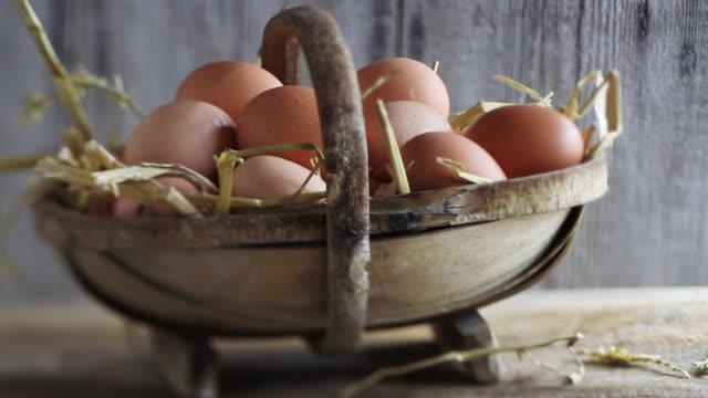 MS PAN Shot of eggs in straw in rustic basket / London, United Kingdom