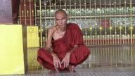 MS Shot of Elderly monk sitting on floor in front of golden gate / Yangon, Yangon Division, Myanmar