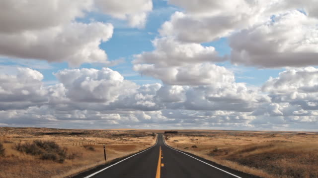 WS Shot of empty highway on vast horizon with puffy clouds / Moses Lake, Washington, United State