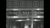 Shot of entrance to Pathe Building / executives sitting in film projection room waiting to watch film film projector starts running and lights are...