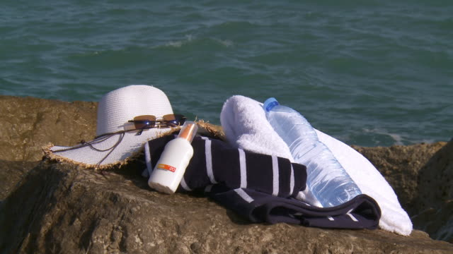 MS Shot of Essentials for day under sun on rock / Marbella, Andalusia, Spain