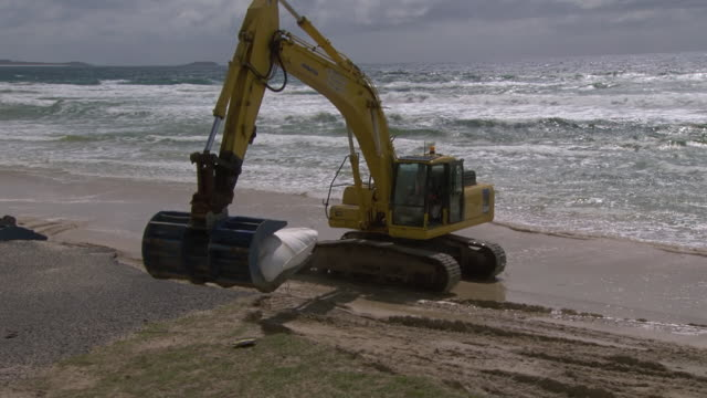 MS TS Shot of Excavator dropping sandbags on beach / Kingscliff, New South Wales, Australia