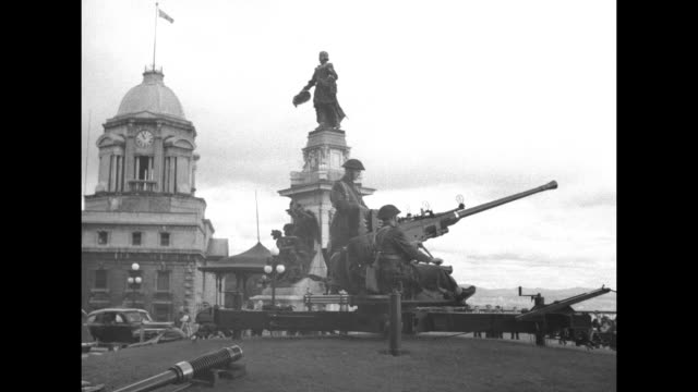 Shot of exterior of Chateau Frontenac / three shots of three Canadian soldiers maneuvering antiaircraft gun near hotel / shot of exterior of hotel...