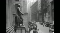 Shot of exterior of Federal Hall on Wall Street people walking on sidewalks in foreground / crowd of men gathered in front of New York Stock Exchange...