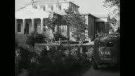 Shot of exterior of Soviet Embassy guard standing on porch / shot from moving car of car in front of it approaching Embassy / shot from moving car as...