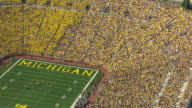 MS AERIAL ZI Shot of fans in stadium and football players on field at Michigan Stadium during game / Ann Arbor, Michigan, United States