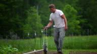 MS SLO MO TS Shot of Farmer planting seeds at organic farm / Chatham, Michigan, United States
