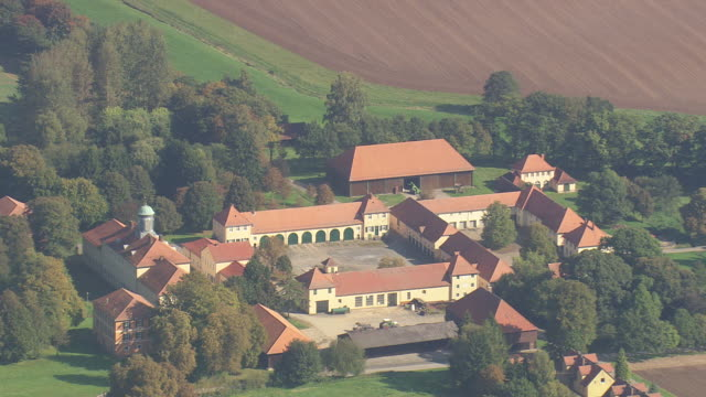 MS AERIAL Shot of farms buildings with trees and farmland / Germany