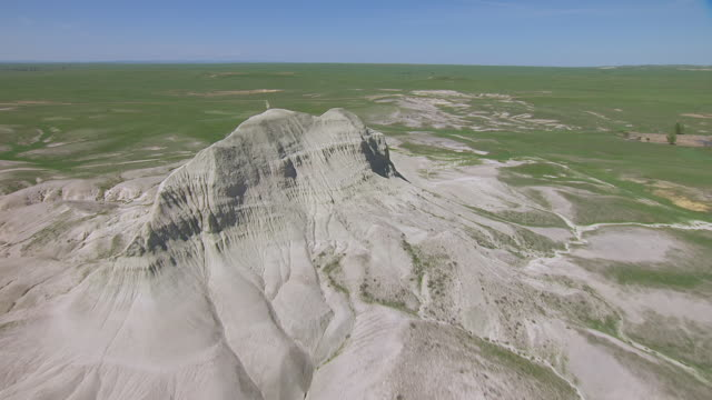 MS AERIAL LA TU TD Shot of Fast over grass to reveal rock formation at Toadstool Geologic Park / Nebraska, United States
