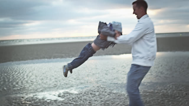 MS Shot of father turning his young child around at beach / St. Peter Ording, Schleswig Holstein, Germany