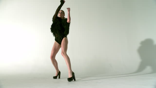 WS SLO MO Shot of female Caucasian dancer wearing black high heels and black leotard with fur top, turning to side, turning around with dance moves / Studio, New York, United States