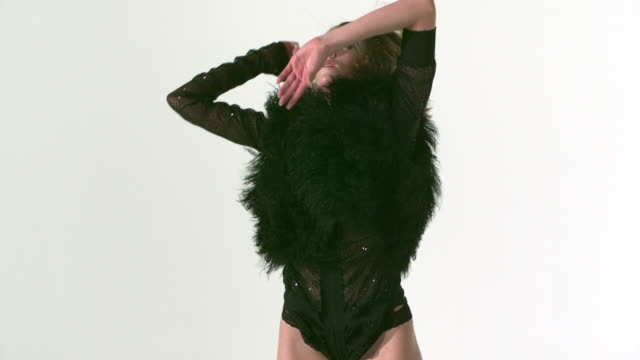 MS ZO ZI SLO MO Shot of female Caucasian dancer wearing black leotard with fur top with arms raised in air and dancing then turning to side and then around with dance moves / Studio, New York, United States