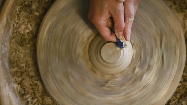 CU Shot of female potter are sharpened bowl with pottery wheel in studio / Kyoto, Japan