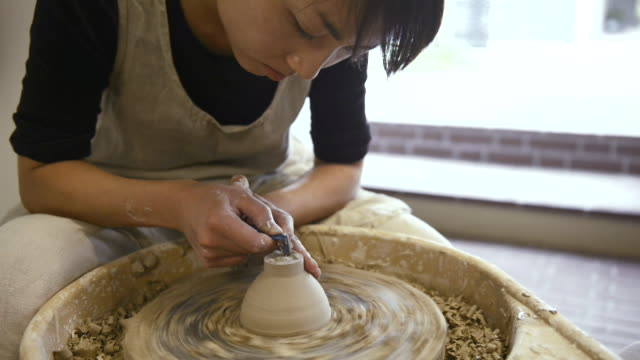 MS Shot of female potter are sharpened bowl with pottery wheel in studio / Kyoto, Japan