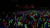 MS CS POV Shot of Festival crowd with giant glow sticks at night / Victoria Park, London, United Kingdom
