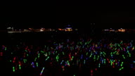 WS CS TD Shot of Festival crowd with giant glow sticks at night / Victoria Park, London, United Kingdom
