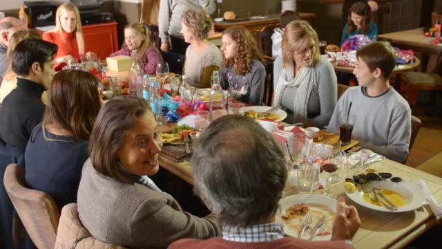 MS TU Shot of Festive lunch in pub with Three generations of family, Granddad and Two grandmas and Two dads and Two mums and Three girls and a boy / London, England, United Kingdom