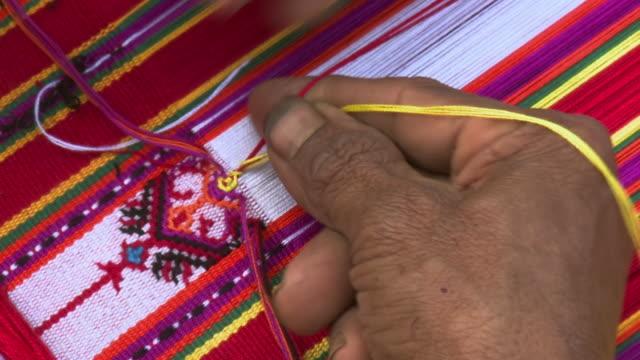 ECU Shot of Fingers weaving beautiful garment / Soe, Mt. Mutis, West Timor Indonesia