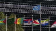MS TU Shot of flags of several countries flying in front of the United Nations headquarters