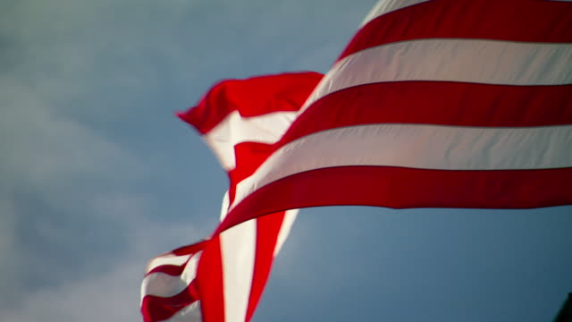 MS ZO Shot of flapping United States flag in wind with smaller black flag below and sunny / Washington, District of Columbia, United States