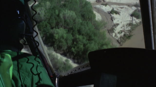MS POV Shot of flying helicopter over rural area and with river