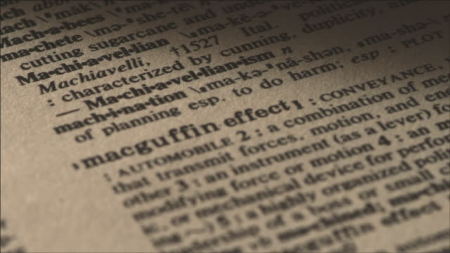 Shot of Focusing Magnifying Glass to look at the definition of a word(Macguffin effect) in dictionary