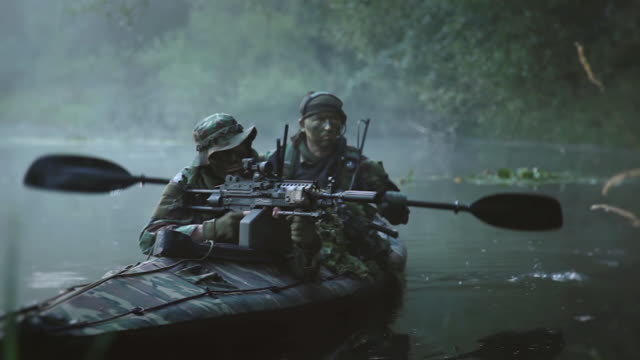MS Shot of Force Recon soldiers in camouflaged folding boat moving in river during reconnaissance mission in jungle with light machine gun in his arms / Swamp, Virginia, United States