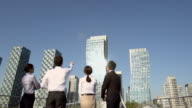 MS SLO MO TU PAN Shot of four business people looking at buildings / Incheon, South Korea