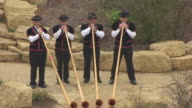 CU AERIAL Shot of four Swiss dressed alphorn blowers / New Glarus, Wisconsin, United States