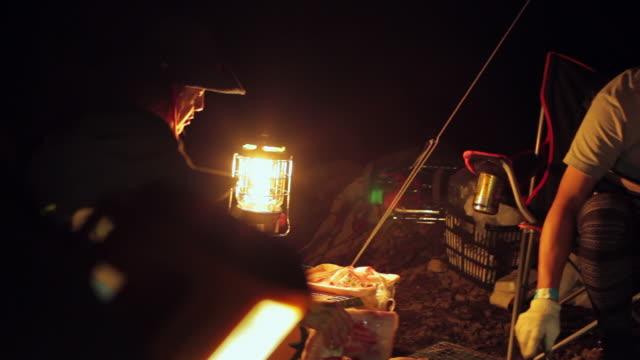MS PAN Shot of friends camping at night in lamp / Okutama, Tokyo, Japan