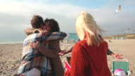 MS SLO MO TU Shot of friends meeting at beach, hugging / Venice, California, United States