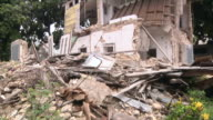 MS TU Shot of from piles of rubble on ground to skeleton of collapse house / Port-au-Prince, Haiti