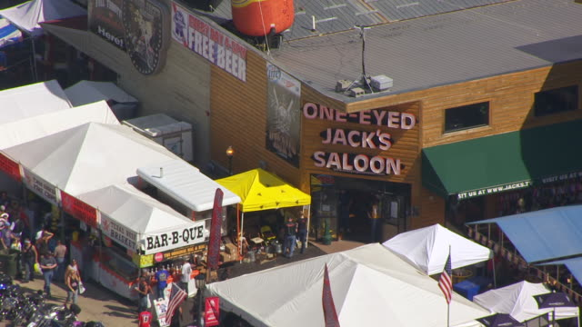 MS AERIAL TS ZO Shot of front of One Eyed Jacks Saloon and pull out to reveal bikes lined up on streets and downtown / Sturgis, South Dakota, United States