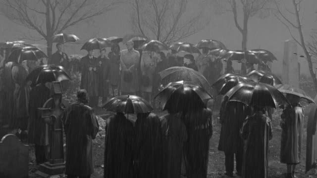 MS Shot of funeral at cemetery people standing around grave in rain holding umbrellas
