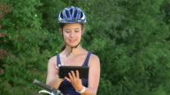 MS shot of girl having rest and looking at tablet with cycle / Ockfen, Rhineland Palatinate, Germany