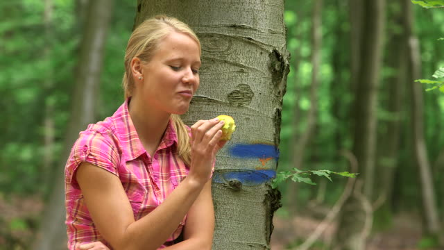 MS Shot of girl having rest in wood land with eating apple / Kastel Staadt, Rhineland Palatinate, Germany