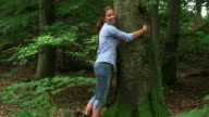 MS Shot of girl hugging tree in wood land / Kastel Staadt, Rhineland Palatinate, Germany