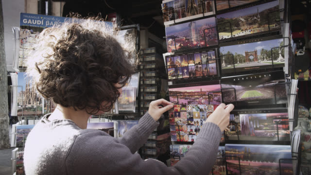 MS Shot of girl looking at postcards / Barcelona, Catalunya, Spain