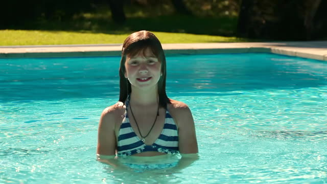 MS Shot of girl smiling in swimming pool / Pollenca Mallorca, Spain