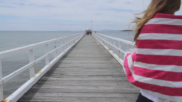 MS Shot of Girl wrapping in towel and walking on pier at great ocean road / Point Lonsdale, Victoria, Australia