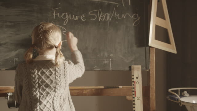 MS ZI Shot of girl writing something on blackboard / Grossweil, Bavaria, Germany