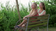 MS Shot of girls in park sitting on bench and laughing / Losheim am See, Saarland, Germany