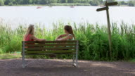 WS Shot of girls in park sitting on bench and talking each other / Losheim am See, Saarland, Germany