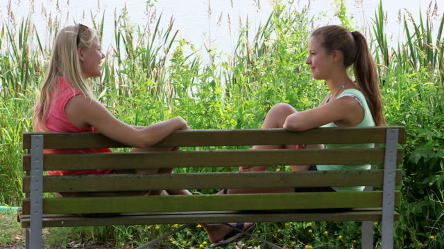 MS Shot of girls in park sitting on bench and talking with each other / Losheim am See, Saarland, Germany