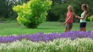 MS Shot of girls in park walking in field of flowers / Losheim am See, Saarland, Germany