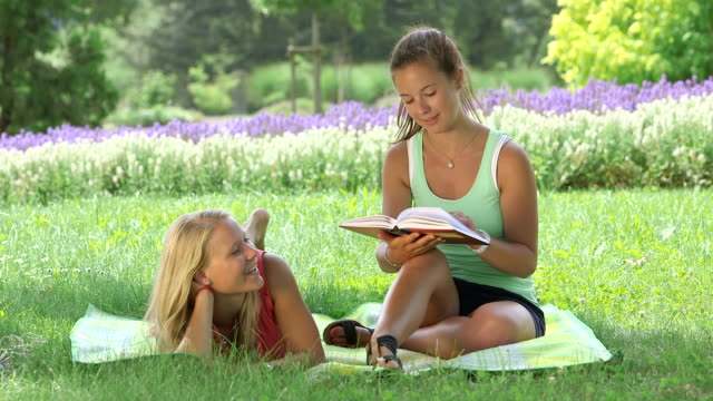 MS Shot of girls laying in park on blanket reading book and talking with each other/ Losheim am See, Saarland, Germany