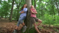 MS Shot of girls leaning against tree in wood land / Kastel Staadt, Rhineland Palatinate, Germany