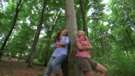 MS TU Shot of girls leaning against tree in wood land / Kastel Staadt, Rhineland Palatinate, Germany