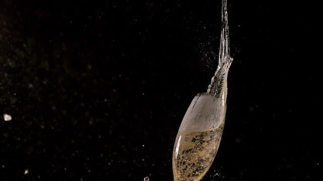 MS SLO MO Shot of Glass of champagne falling, breaking and splashing against black background / Calvados, Normandy, france
