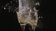 MS SLO MO Shot of Glasses of champagne breaking and splashing against black background / Calvados, Normandy, france